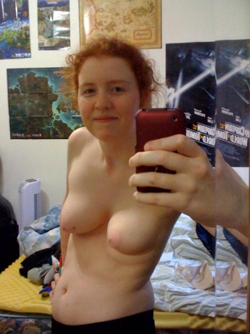 Une rousse sexe exhibe ses seins avec son téléphone portable