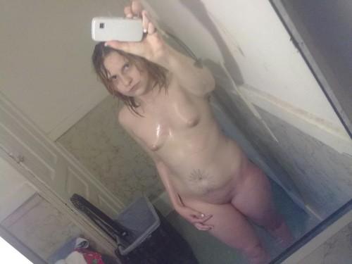 une femme nue sous la douche se prend en photo